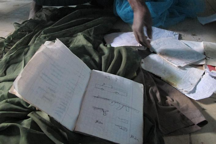 In this Wednesday, Feb. 6, 2013 photo, neighborhood resident Mohamed Alassane sifts through documents left behind at the Ministry of Finance's Regional Audit Department, in Timbuktu, Mali, where a confidential letter was found from terror leader Abdelmalek Droukdel spelling out the terror network's blueprint for conquering this desert nation. In the days before being rousted by a French assault force, the leader of al-Qaida¹s branch in Africa had warned fellow Islamic fighters to go softly on the people in order to make their takeover of northern Mali last. The more than 10-page letter, which the AP found in a building the Islamists occupied for nearly a year, is signed by Droukdel, the senior commander appointed by Osama bin Laden to run al-Qaida's branch in Africa. (AP Photo/Rukmini Callimachi)