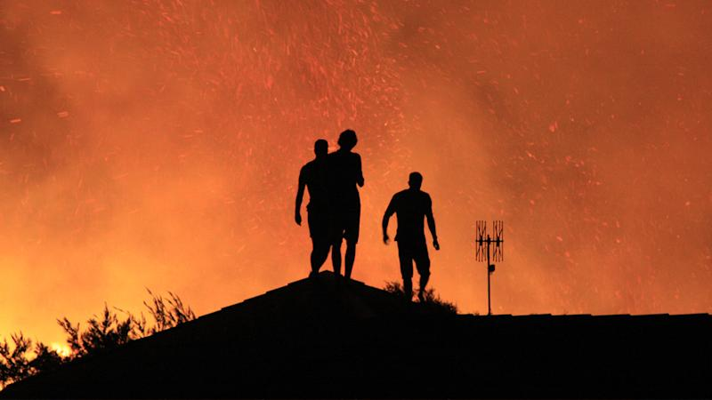 Residents pictured standing on their rooftop as bushfires rage at Sunshine Beach in the Noosa National park