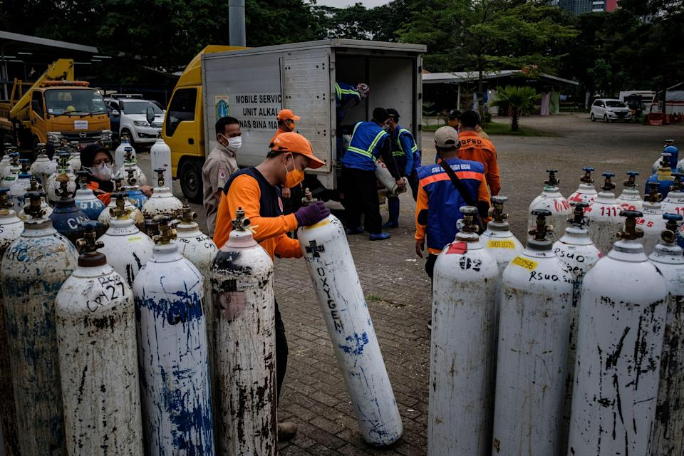 Members of Indonesia's national rescue organisation offload oxygen tanks to be distributed to hospitals in Jakarta on 13 July 2021 (Getty Images)