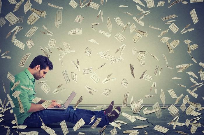 A man looks at his laptop as cash money falls around him.