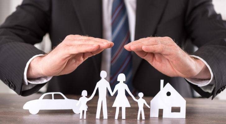 Man in suit with hands over paper cutouts of family, car and home. Represents insurance.