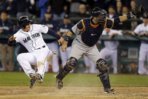 Seattle Mariners' Kyle Seager, left, leaps up after sliding safely into home as Detroit Tigers catcher Alex Avila makes his case to the umpire in the seventh inning of a baseball game, Thursday, April 18, 2013, in Seattle. (AP Photo/Ted S. Warren)