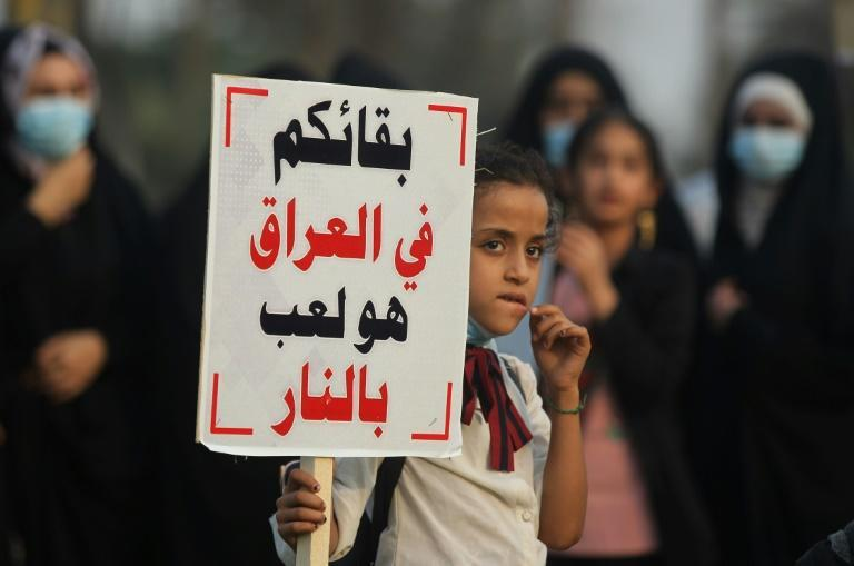 "A girl carries a sign reading in Arabic ""remaining in Iraq is playing with fire"", a message directed at the US military, during a demonstration outside the the Iraqi capital's highly-fortified Green Zone on Saturday"