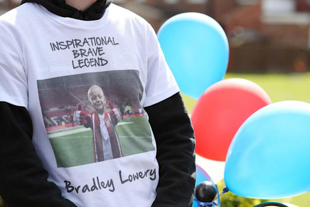<p>People line the route of the funeral procession with decorations ahead of the funeral of Bradley Lowery, the six-year-old football mascot whose cancer battle captured hearts around the world </p>