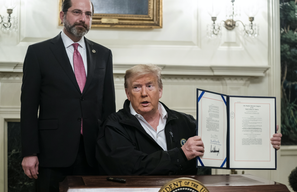 U.S. President Donald Trump, right, holds up a signed emergency coronavirus spending bill with Alex Azar, secretary of Health and Human Services (HHS), in the Diplomatic Room of the White House in Washington, D.C., U.S., on Friday, March 6, 2020. (Photo: Jim Lo Scalzo/EPA/Bloomberg via Getty Images)