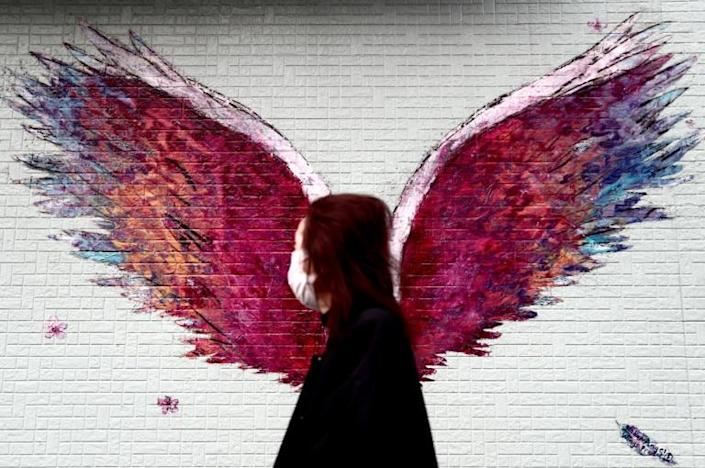 A woman wearing a face mask amid concerns over COVID-19 walks past a graffiti of wings in Tokyo (AFP Photo/Behrouz MEHRI)