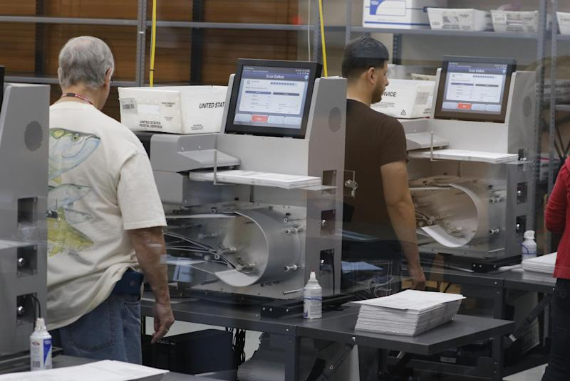 Florida elections staff load ballots into machines as the statewide vote recount is being conducted to determine the races for governor, Senate, and agriculture commissioner: Joe Skipper/Getty Images