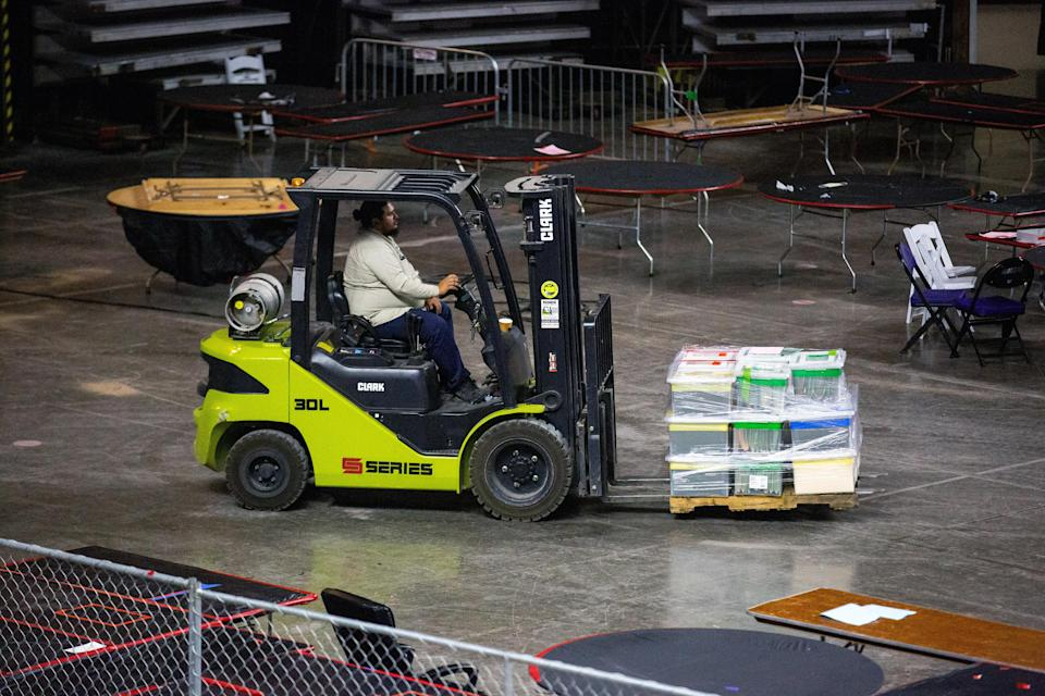 A contractor working for Cyber Ninjas moves boxes containing vote tallies to a truck for storage during the company's audit of 2020 election results in Phoenix, Ariz., on May 14, 2021. (Courtney Pedroza/The New York Times)