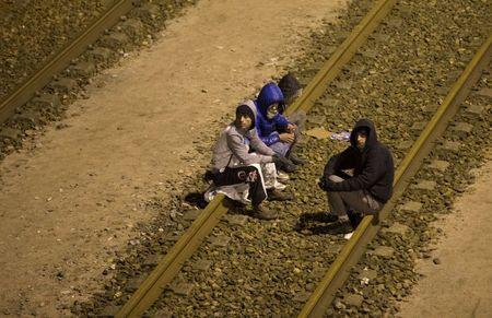 Migrants sit on the railway tracks of the freight shuttle leading to the entrance of the Channel Tunnel in Calais, France, October 14, 2015. REUTERS/Philippe Wojazer