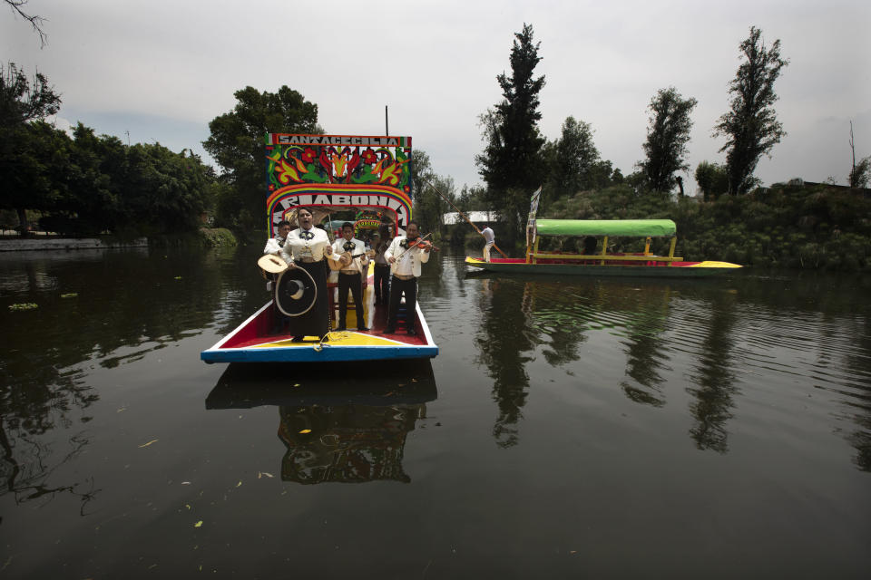 Mariachis perform on one of the painted wooden boats, known as a trajinera, popular with tourists that ply the water canals in the Xochimilco district of Mexico City, after all activities had been on pause for the past six months due to the COVID-19 pandemic. (AP Photo/Marco Ugarte)