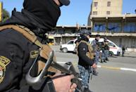 Security forces stand guard after twin suicide blasts killed at least 32 people and wounded more than 100 in Baghdad on January 21, 2021