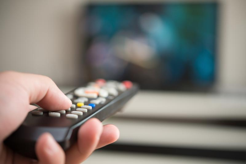 Close-up shot of a hand holding a TV remote, with the TV set visible in the blurry distance.