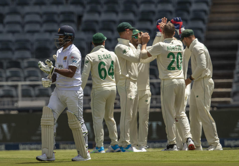 Sri Lanka's captain Dimuth Karunaratne, left, leaves the field after being dismissed by South Africa's bowler Anrich Nortje, second from right, during the 2nd Test cricket match between South Africa and Sri Lanka in Johannesburg, South Africa, Sunday, Jan. 3, 2021. (AP Photo/Themba Hadebe)