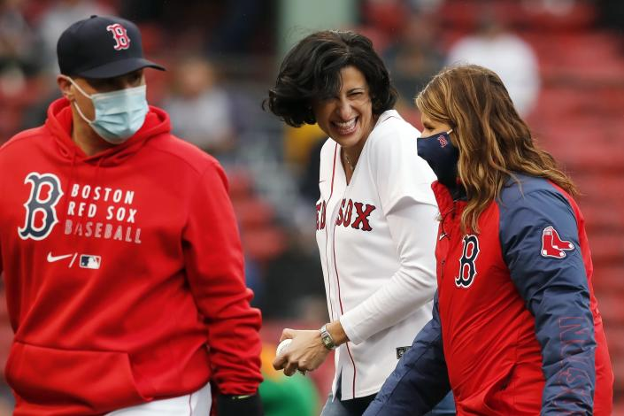 Director of the Centers for Disease Control and Prevention Rochelle Walensky, center, walks off the field after throwing out the ceremonial first pitch to Boston Red Sox's Christian Vazquez, left, before a baseball game against the Miami Marlins, Saturday, May 29, 2021, in Boston. (AP Photo/Michael Dwyer)