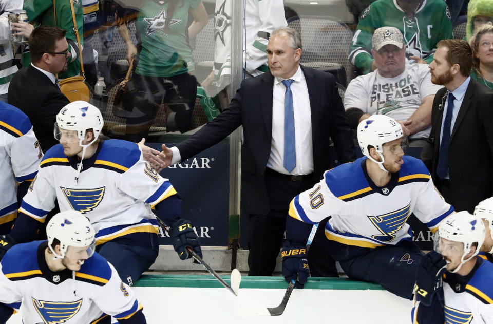 St. Louis Blues interim head coach Craig Berube, center, shakes hands with staff, celebrating the team's 4-1 win against the Dallas Stars in Game 6 of an NHL second-round hockey playoff series in Dallas, Sunday, May 5, 2019. (AP Photo/Tony Gutierrez)