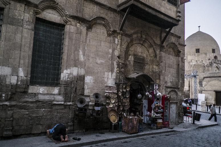 A man (left) prays outside his bazaar shop after breaking the day-long fast during the holy month of Ramadan in Cairo's Khan el-Khalili district on July 8, 2014 (AFP Photo/Khaled Desouki)