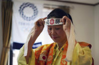 """Olympic fan Kyoko Ishikawa wears a cheering headband with Japanese words """"Confident victory"""" around her head Saturday, April 10, 2021, in Tokyo. Ishikawa, president of an IT company, has attended every Summer Olympics since Barcelona in 1992, becoming famous as an unofficial """"International Olympic Cheerleader."""" She relishes joining in with fans from everywhere to cheer for their athletes. (AP Photo/Eugene Hoshiko)"""