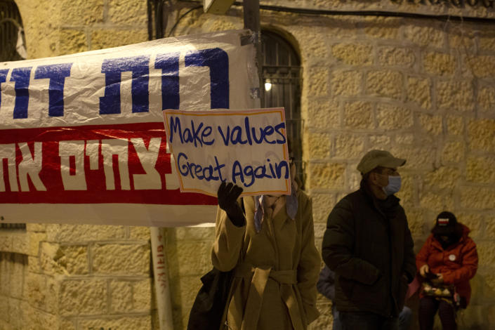 A protester holds a placard outside of Israeli Prime Minister Benjamin Netanyahu's official residence in Jerusalem, Saturday, Jan. 16, 2021. (AP Photo/Maya Alleruzzo)