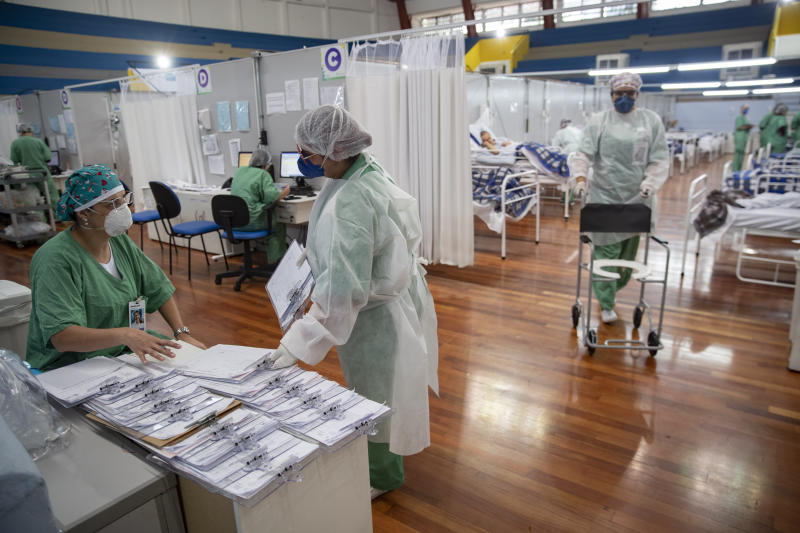 Health personnel work in a field hospital built inside a gym to treat COVID-19 patients in Santo Andre, on the outskirts of Sao Paulo, Brazil, Tuesday, June 9, 2020. (AP Photo/Andre Penner)