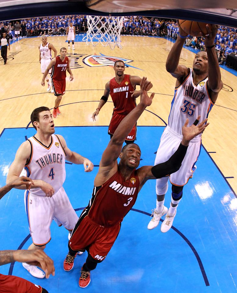 OKLAHOMA CITY, OK - JUNE 12:  Kevin Durant #35 of the Oklahoma City Thunder goes up for a layup over Dwyane Wade #3 of the Miami Heat in the second half in Game One of the 2012 NBA Finals at Chesapeake Energy Arena on June 12, 2012 in Oklahoma City, Oklahoma. NOTE TO USER: User expressly acknowledges and agrees that, by downloading and or using this photograph, User is consenting to the terms and conditions of the Getty Images License Agreement.  (Photo by Ronald Martinez/Getty Images)