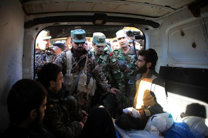 A Syrian pro-government fighter who was wounded during a battle, is evacuated from the Kweyris military air base, in the northern Syrian province of Aleppo, on November 11, 2015 (AFP Photo/George Ourfalian)