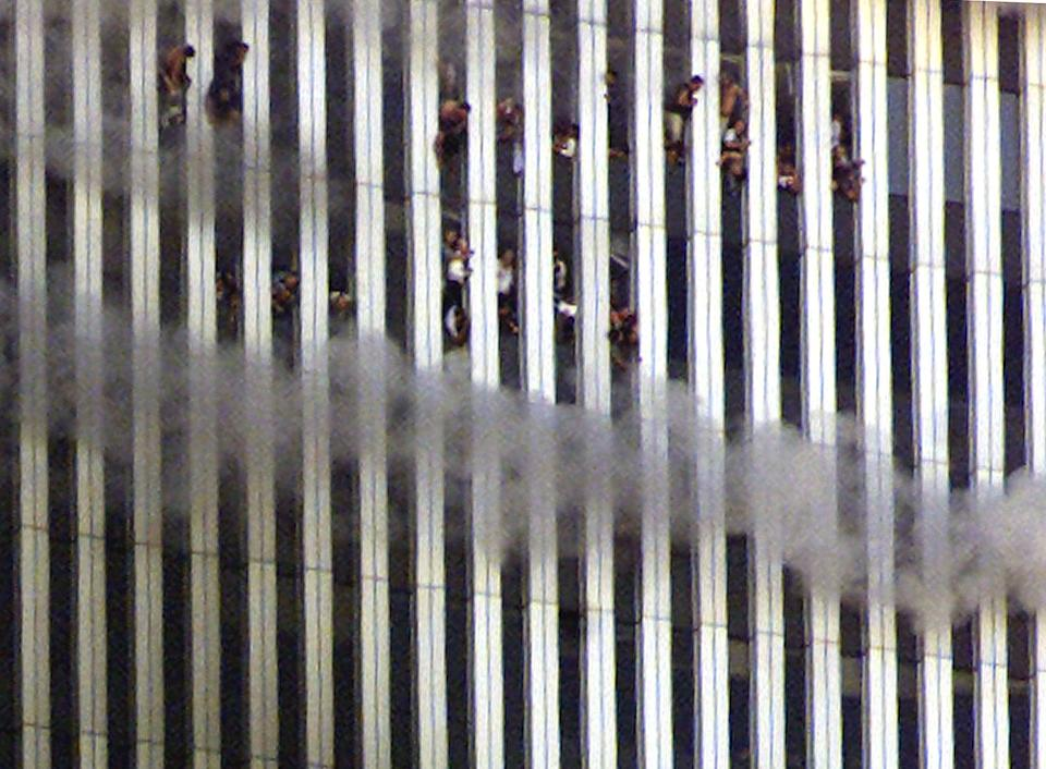 <p>People look out of the burning North tower of the World Trade Center. Both towers were hit by planes crashing into the buildings. Shortly after this photo was taken this tower fell. (Reuters)</p>