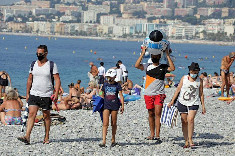 Tourists wearing protective face masks walk on the beach in Nice: REUTERS