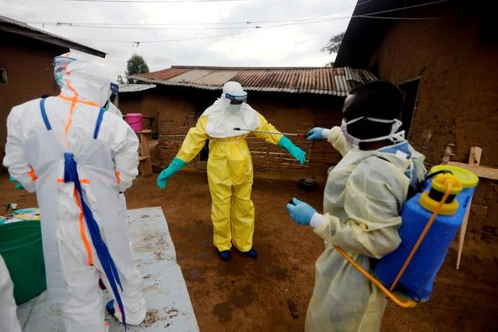 FILE PHOTO: Healthcare worker Kavota Mugisha Robert decontaminates his colleague after he entered the house of 85-year-old woman suspected of dying of Ebola in the eastern Congolese town of Beni