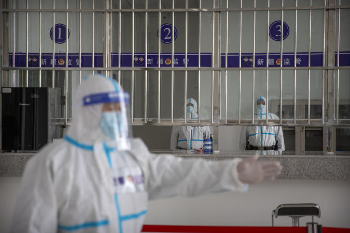 A security officer in a protective suit gestures as other officers stand at a reception area at the visitors' hall at the Urumqi No. 3 Detention Center in Dabancheng in western China's Xinjiang Uyghur Autonomous Region on April 23, 2021. (AP Photo/Mark Schiefelbein)