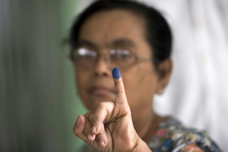 A woman shows her finger, which was inked after she cast her vote in a by-election, in a  polling station in Yangon, Myanmar