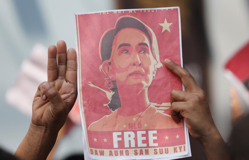 Myanmar nationals living in Thailand hold pictures of Myanmar leader Aung San Suu Kyi gesture with a three-fingers salute, a symbol of resistance, as they protest in front of the Myanmar Embassy in Bangkok, Thailand, Monday, Feb. 8, 2021. Myanmar's military announced last week that it will take power for one year, accusing leader Aung San Suu Kyi's government of not investigating allegations of voter fraud in recent elections. (AP Photo/Sakchai Lalit)