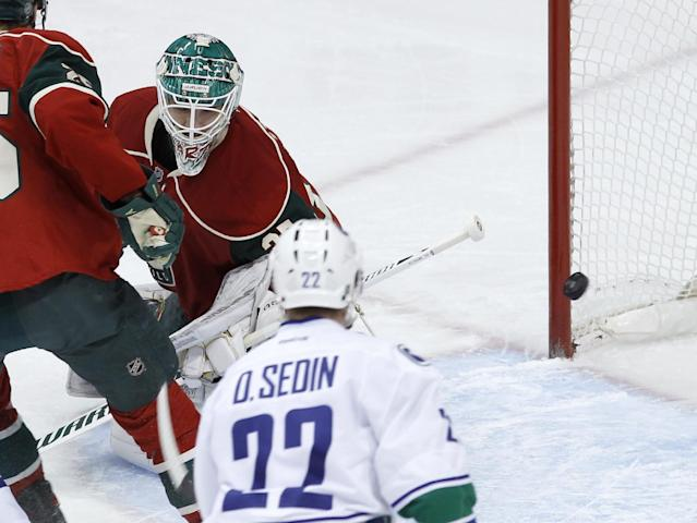 Vancouver Canucks left wing Daniel Sedin (22), of Sweden, watches as a shot by Canucks right wing Jannik Hansen gets past Minnesota Wild goalie Josh Harding (37) during the first period of an NHL hockey game in St. Paul, Minn., Tuesday, Dec. 17, 2013. (AP Photo/Ann Heisenfelt)