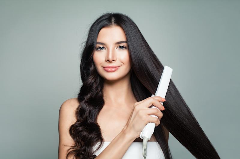 Attractive Woman with Curly Hair and Long Straight Hair Using Hair Straightener as Kmart $20 budget buy sparks debate