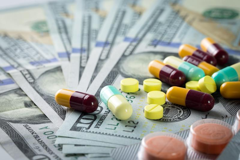 Medications scattered on top of $100 bills