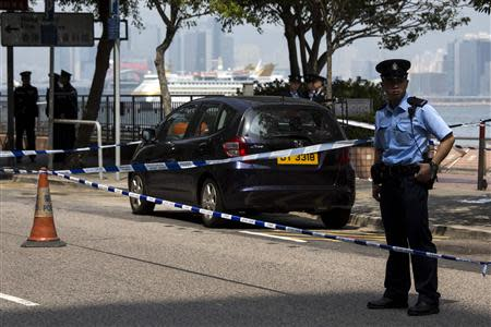 A policeman stands guard next to former Ming Pao chief editor Kevin Lau's car after Lau suffered from a chopper attack in Hong Kong February 26, 2014. REUTERS/Tyrone Siu