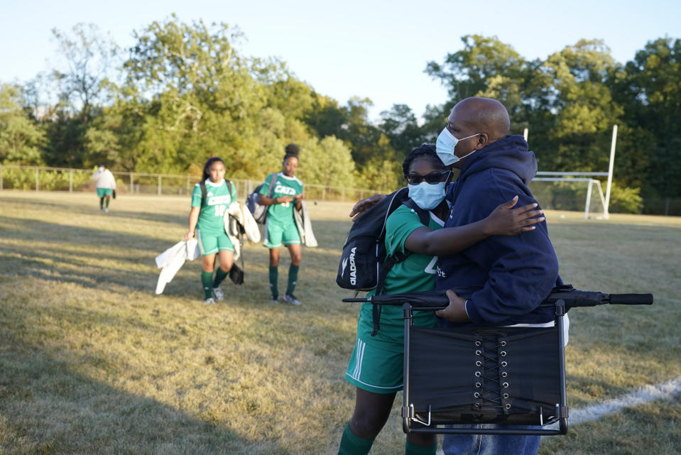 Larry Brown, hugs his daughter, Justys Glenn, right, following a soccer game, Wednesday, Sept. 30, 2020, in Indianapolis. Larry Brown spent about 80 days in an Indianapolis hospital this spring, fighting COVID-19 and nearly dying. His journey since returning home in June has been filled with unknowns. (AP Photo/Darron Cummings)