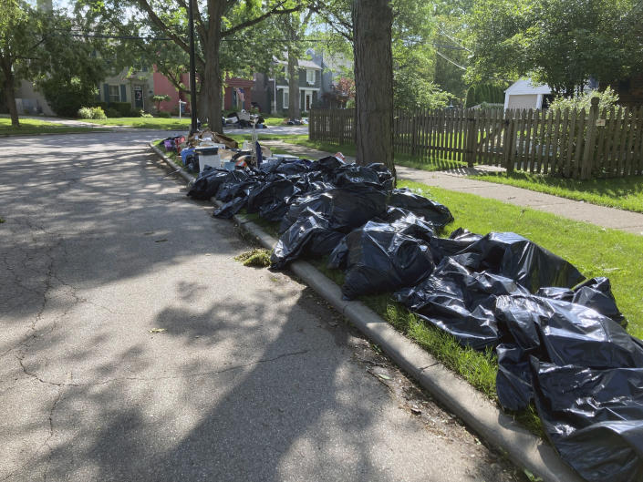 Trash is shown on a street in Grosse Point Farms, Mich., Sunday, June 27, 2021. Residents in the Detroit area were cleaning up Sunday after flooding in the area overloaded sewer systems, damaged homes and knocked out power for thousands. (AP Photo/Ed White)