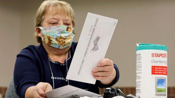 PHOTO: Election volunteer Nancy Gavney verifies voter and witness signatures on absentee ballots as they are counted at the City Hall during the presidential primary election held amid the coronavirus disease outbreak in Beloit, Wis., April 7, 2020. (Daniel Acker/Reuters, FILE)