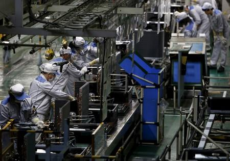 FILE PHOTO: A Daikin Industries Ltd employee works the production line of outdoor air conditioning units at the company's Kusatsu factory in Shiga