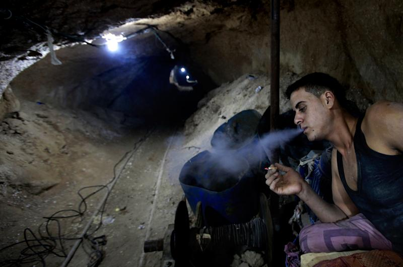 In this Monday, Sept. 30, 2013 photo, a Palestinian worker smokes a cigarette inside a smuggling tunnel along the border with Egypt in Rafah, southern Gaza Strip. Gaza's tunnel smugglers along the border with Egypt are mostly idle these days. Some rest on cots in the dank underground pathways, stretching out for a smoke. Others pass the time cleaning the small carts on wheels that are normally pulled through the tunnels carrying cement or consumer goods from Egypt. Since the summer, Egypt's military has tried to destroy or seal off most of the smuggling tunnels under the Gaza-Egypt border, a consequence of the heightened tensions between Cairo and the Hamas government in Gaza. (AP Photo/Hatem Moussa)