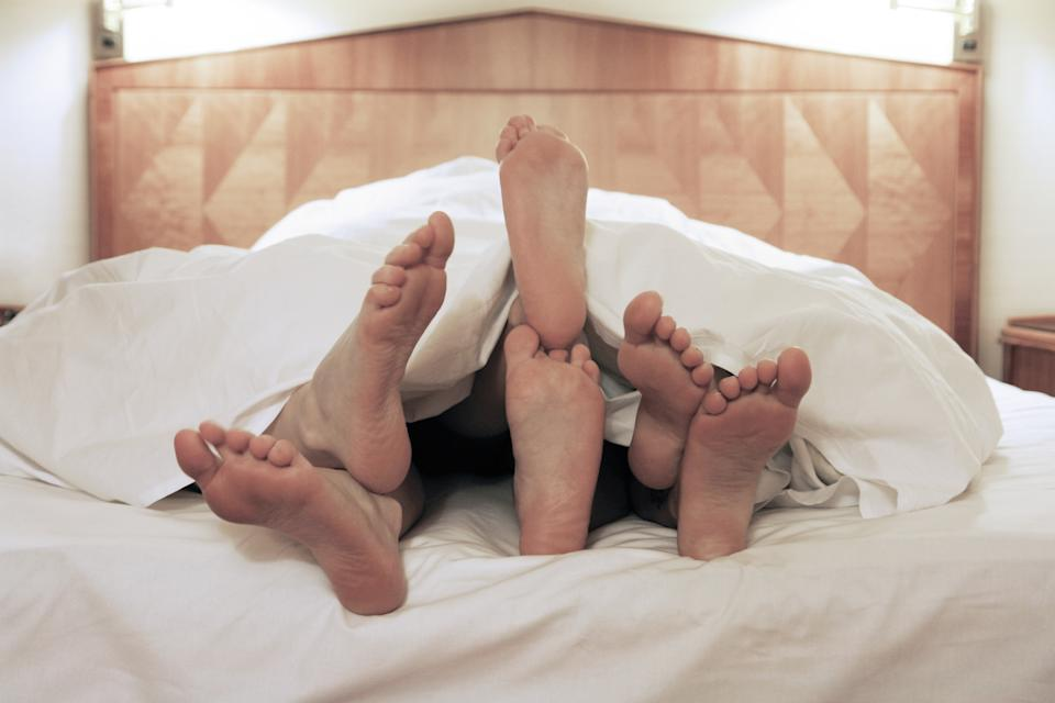 Three People Under Blanket On Bed