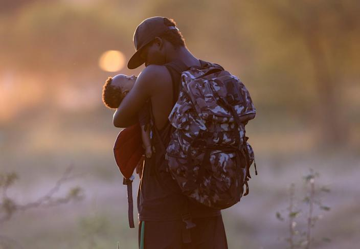 An exhausted Haitian father cradles his son on the Mexican side of the Rio Grande