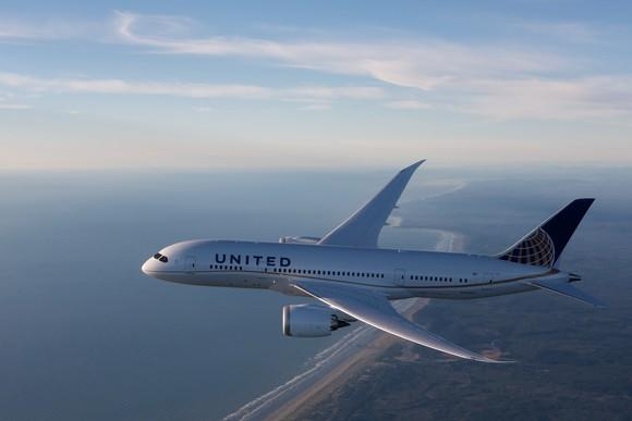 A United Airlines Dreamliner flying over a coastline