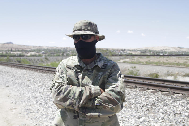 An self-styled Patriot stands a quarter mile from a barrier that marks the U.S.-Mexico border Tuesday, April 23, 2019, in Sunland Park, N.M., hours before being removed from his group's campsite by police. Members of the United Constitutional Patriots gained national attention after filming themselves detaining immigrants who cross the border to the east where the wall ends. (AP Photo/Cedar Attanasio)