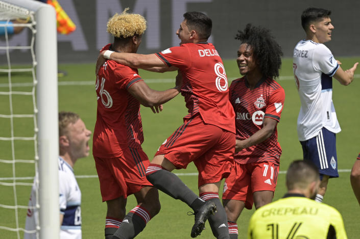 Toronto FC defender Luke Singh (26) is congratulated by midfielder Marco Delgado (8) and forward Jayden Nelson (11) after Singh scored a goal during the first half of an MLS soccer match against the Vancouver Whitecaps, Saturday, April 24, 2021, in Orlando, Fla. (AP Photo/Phelan M. Ebenhack)