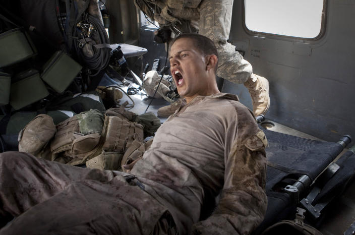 """Lance Cpl. Blas Trevino of the 1st Battalion, 5th Marines, shouts out as he is rescued on a medevac helicopter from the U.S. Army's Task Force Lift """"Dust Off"""", Charlie Company 1-214 Aviation Regiment after he got shot in the stomach outside Sangin, in the Helmand Province of southern Afghanistan on June 11, 2011. The Army's 'Dust Off' crew needed two attempts to get him out, as they were fired upon and took five rounds of bullets into the tail of their aircraft. (AP Photo/Anja Niedringhaus, File)"""