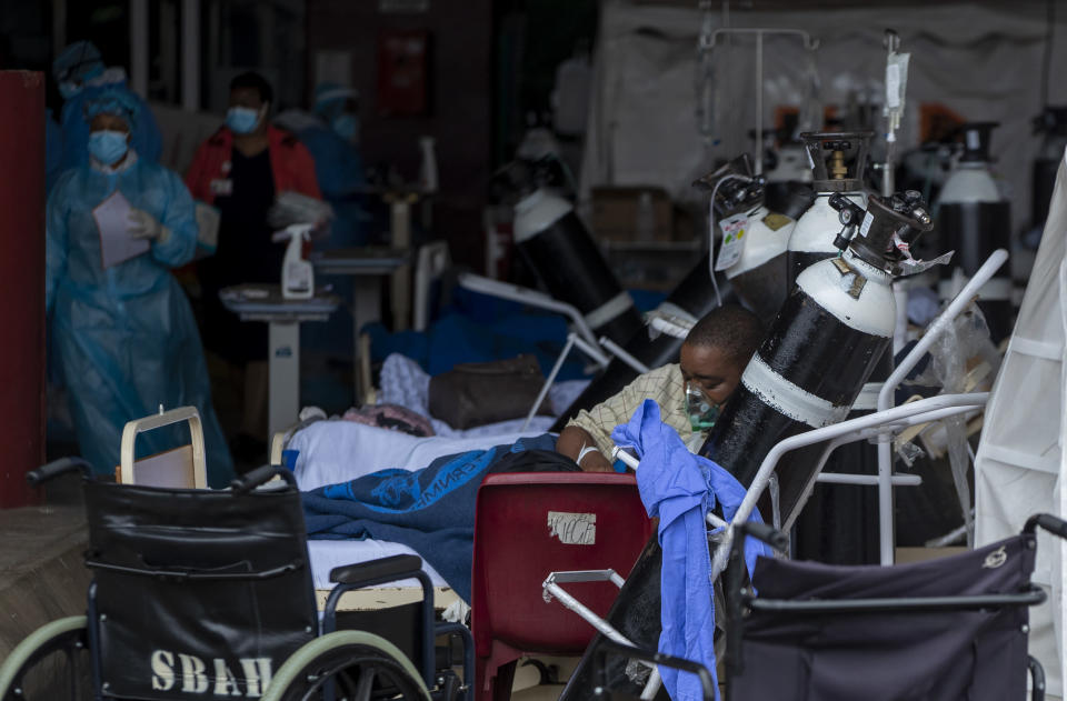 A patient wearing an oxygen mask is being treated in makeshift emergency units at Steve Biko Academic Hospital in Pretoria, South Africa, Monday, Jan. 11, 2021, which is battling an ever-increasing number of Covid-19 patients. (AP Photo/Themba Hadebe)