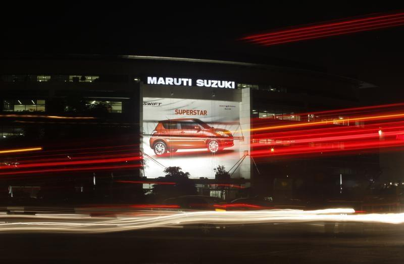 Traffic moves along a busy road in front of the Maruti Suzuki corporate office building in New Delhi
