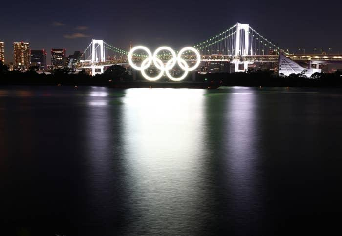 The Olympic rings lit on the side of a bridge at night