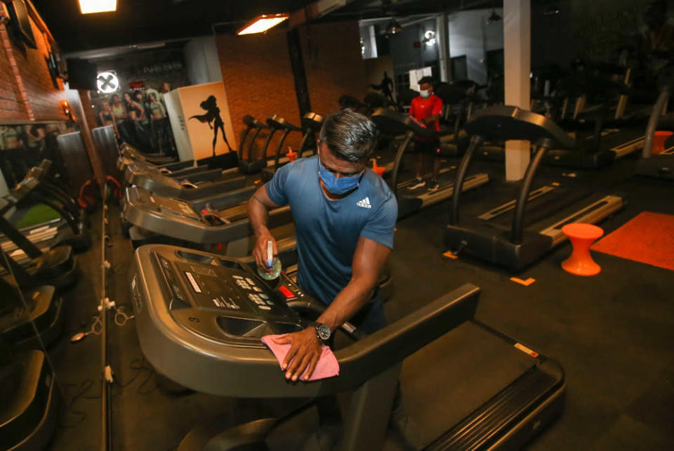 Fitness Lifestyle Gym owner V. Sam Pakiaraj cleans fitness equipment at his gym in Desa Rishah, Ipoh September 1, 2021. — Picture by Farhan Najib